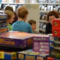 Des enfants jouent derrière des piles de boîtes de jeux de société.