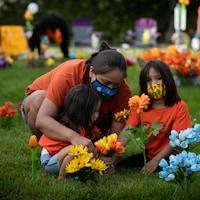 Une femme et deux enfants vêtus d'un chandail orange sont accroupis dans le gazon et tiennent un petit bouquet de fleurs.