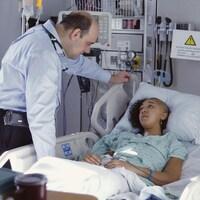 Un docteur parle à une patiente sur son lit d'hôpital.