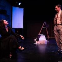Une femme, assise et la main droite dans les airs, regarde un homme debout devant elle. L'homme porte un complet et une cravate. Il a les mains dans les poches.