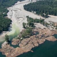 L'eau boueuse remplie de débris d'une rivière se jette dans un lac.