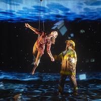 Des acrobates livrent une prestation, baignés dans un univers de projections oniriques.