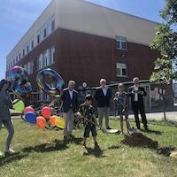 Deux élèves, du personnel de l'école et le maire de Val-d'Or tiennent des ballons ou font une pelletée de terre.
