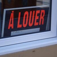 Une pancarte «À louer» dans la fenêtre d'un logement.