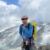 Steven Song en montagne, muni d'un équipement d'alpinisme.