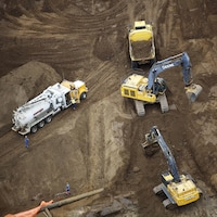 De la machinerie lourde en action dans une mine de sables bitumineux, près de Fort McMurray, dans le nord de l'Alberta.