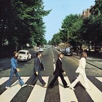 Les quatre membres de Beatles marchent l'un derrière l'autre sur un passage piéton.
