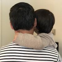 Un homme vu de dos tient son enfant dans ses bras.