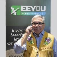 Abel Bosum parle au cellulaire devant une affiche d'Eeyou Mobilité.