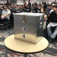 Boîte de votes de l'ABI devant des syndiqués dans une salle.