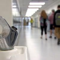 Une fontaine d'eau en premier plan et des élèves qui marchent au loin dans un corridor.