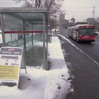 Un autobus d'OC Transpo s'apprête à passer devant un arrêt vide.