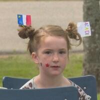 Une jeune fille aux cheveux roux avec des drapeaux acadiens sur la tête.