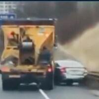 Un camion orange pousse une voiture grise sur chaussée.