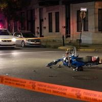 Un cyclomoteur et un vélo sont imbriqués l'un dans l'autre, au milieu de la chaussée.