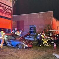 Une voiture endommagée et une personne sur une civière.