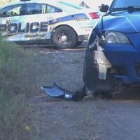 Une voiture bleue et un morceau cassé en bordure de la chaussée.
