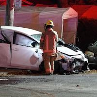 Deux voitures embouties derrière un pompier, de dos.