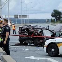 Scène d'un accident de voiture. On voit une voiture complètement cabossée et brisée de partout, une autopatrouille de police et des policiers en uniforme dans un périmètre délimité par un ruban interdisant le passage. Des débris jonchent le sol.