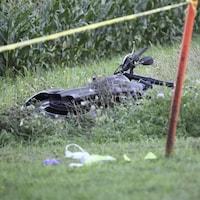 Une moto est couchée dans l'herbe.