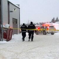 Deux policiers marchent dans la neige près de l'édifice de Pièces d'autos choc.
