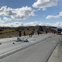 Des pompiers ramassent des débris sur la route sur le site d'un accident.