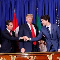 Le président américain Donald Trump, entouré d'Enrique Pena Nieto et de Justin Trudeau qui se serrent la main.