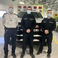 Des paramédics posent devant une ambulance.