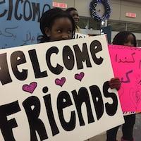 Une fille tient une pancarte où il est inscrit « bienvenue à nos amis », pour accueillir un groupe de réfugiés syriens à l'aéroport de Regina.