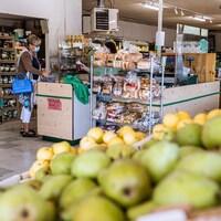 Une femme achète de la nourriture dans un petit marché. Des poires sont en premier plan.