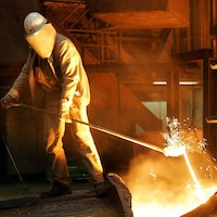Un travailleur de l'acier habillé d'une combinaison manipule de l'acier en fusion.