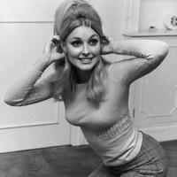 La jeune femme touche ses oreilles avec ses mains et sourit dans une photo en noir et blanc.