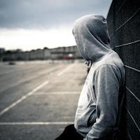 Une personne portant un chandail avec une capuche qui cache son visage est adossée à une clôture, seule.