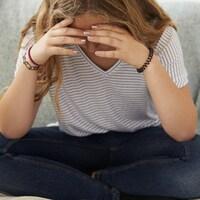 Une jeune fille est assise sur un sofa et tient sa tête dans ses mains.