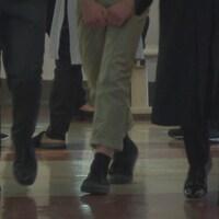 Les jambes d'individus qui marchent dans une salle.