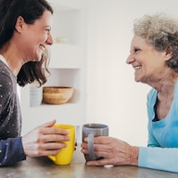 Une femme adulte et sa mère âgée devant des tasses de café.