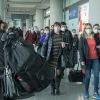 Des passagers portant un masque font la file dans un aéroport.