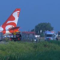 Des véhicules de police près d'un tarmac d'avions.