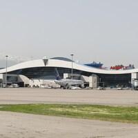 Le terminal de l'aéroport est situé devant des montagnes enneigées.