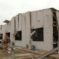 Un soldat debout devant un bâtiment endommagé,