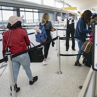 Des voyageurs attendent pour s'enregistrer.