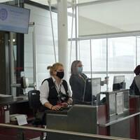Un passager montre son billet à deux agentes de bord.