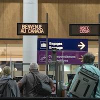 Des passagers avancent vers l'accueil aux douanes canadiennes à l'aéroport international Trudeau à Montréal pour les formalités d'entrée au pays.