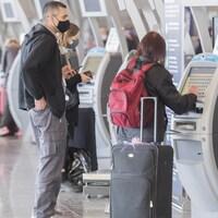 Des voyageurs avec leurs valises à l'aéroport Trudeau.