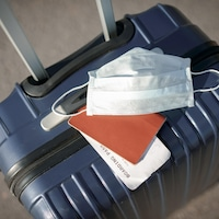Les bagages d'un voyageur. Un masque bleu est posé sur la valise.