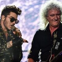 Le chanteur Adam Lambert et Brian May, du groupe Queen, sont sur scène et interprète un des succès du groupe devant un grand écran illuminé.