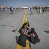 Afghan people sit along the tarmac as they wait to leave the Kabul airport.