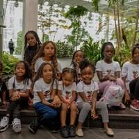 Des enfants noirs entourés de plantes dans un corridor de l'Université de Regina.