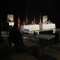 Cinq personnes espacées de deux mètres dans une grande salle. Une personne est au podium.