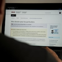 Une personne regarde le site de l'Agence du revenu du Canada sur un écran. La page l'informe qu'il ne peut temporairement consulter son dossier.